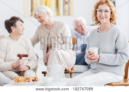 Elegant happy older woman drinking tea in senior club