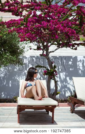 Beautiful Woman Relaxing On Sunbed In Luxury Resort