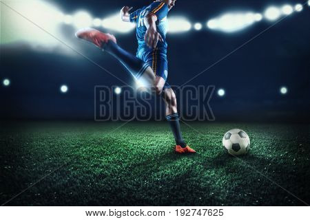 The legs of soccer football player training football on green grass field. Advertising concept of soccer football