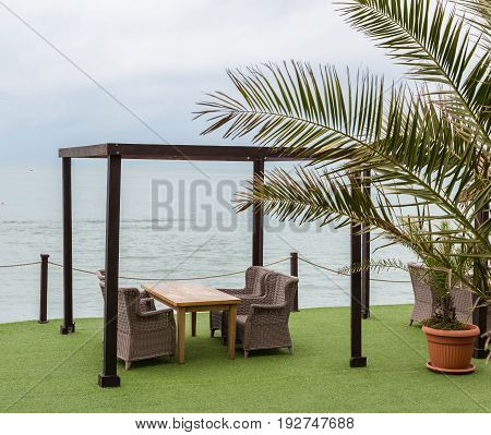 Wooden tables and wicker chairs under a canopy overlooking sea. Palm tree leaves