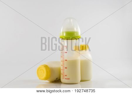 Baby bottle with milk and a measuring scale on the background of a lot of full bottles of breast milk. Mother's milk - the most healthy food for newborn