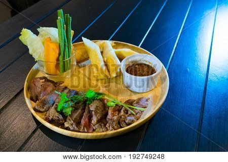 Sliced grilled beef steak with green leaves salad on rustic plate with cutlery. Medium rare barbecue steak and healthy salad on gray stone background top view place for text