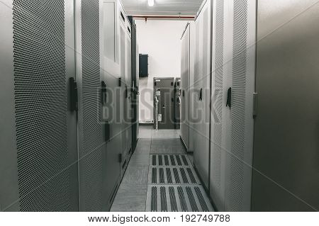 Switchgear room with raws of cabinets with network or cellular hardware, perspective