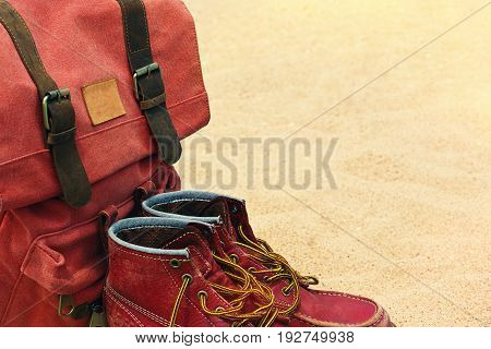 Traveler's worn boots and backpack in retro style left on a sand beach
