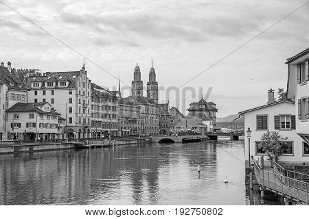 Downtown view of Zurich from bridge Rudolf-Brun-Brucke Grossmunster town hall and river Limmat in front - black and white.