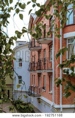 The facade of brick houses with wrought-iron balconies on a background of green leaves