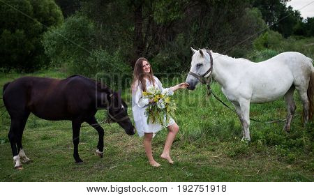 Young beautiful Slavic girl with a wreath in his hands standing near two horses. Holiday of Ivan Kupala.