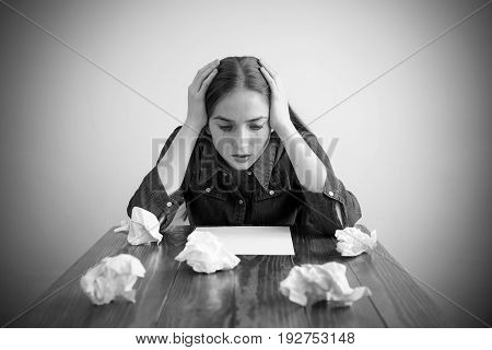 Woman crying over a blank sheet. Manipulated black-and-white image. Vignette is added.