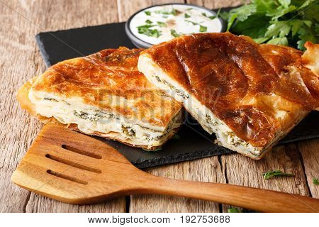 Balkan Burek Stuffed With Spinach And Cheese With Sour Cream Sauce Close-up. Horizontal