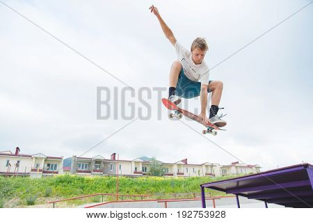 Young intense skateboarder in high jump against the sky and sleeping areas