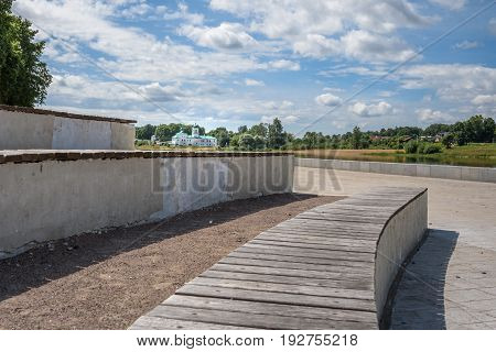 Pskov, summer promenade and benches in front of a river and the Mirozhsky monastery
