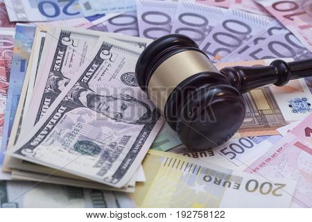 Wooden judge gavel on dollars end euro banknotes