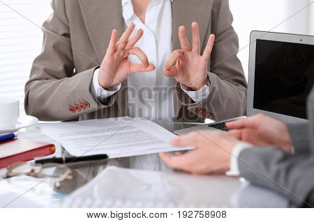 Group of business people or lawyers at meeting discussing contract papers. Woman showing ok sign.