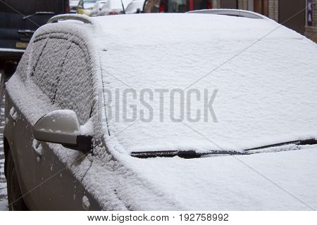 Car covered with snow in winter blizzard