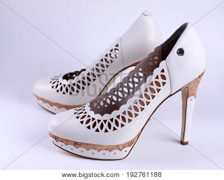 White fashion women's shoes with high heels. Side view, selective focus