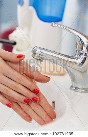 Woman Washing Hands Under Flowing Tap Water In The Bathroom