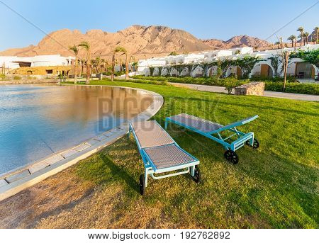 Egypt Dahab - hotel swimming pool with sea water and sun loungers. Early morning