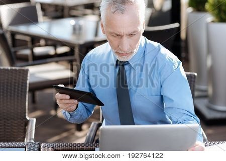 Do not be so serious. Attractive bearded male person holding tablet in right hand and bowing head while looking at screen of his laptop