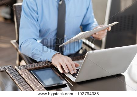 Do it immediately. Competent manager holding folder with documents in left hand and typing text while using keyboard of his laptop