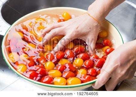 Hand Washing Cherry Tomato With Running Water In Household Sink