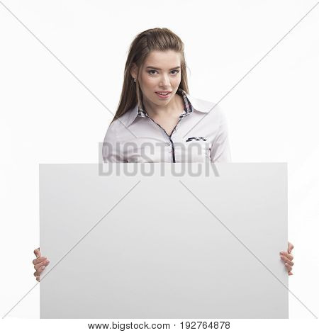 Young confident woman portrait of a confident businesswoman showing presentation, pointing placard gray background. Ideal for banners, registration forms, presentation, landings, presenting concept..