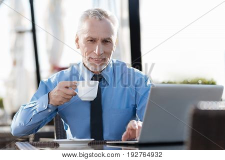 Time for lunch. Handsome retirement holding cup in right hand and putting left one on the laptop while looking straight at camera