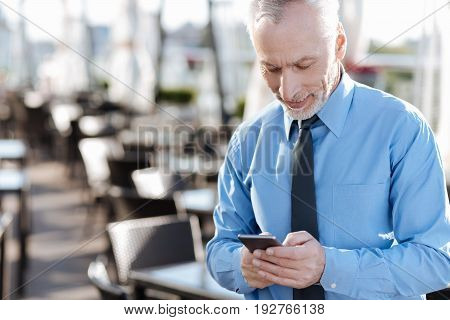 I have break. Handsome gray haired man keeping smile on his face and vowing head while looking at his phone