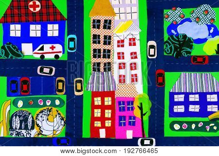 Fabric town: houses hospital and ambulance parks roads and cars made of colorful fabric pieces.
