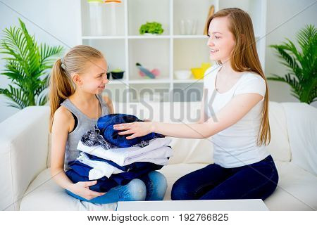 Happy mother and daughter folding laundry together