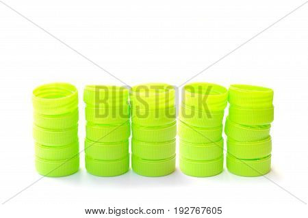 pile of green plastic bottle caps isolated on white background