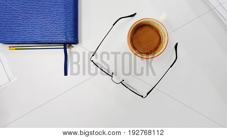 Office work space with eye glasses leather notebook pencil mouse and cup of coffee, Top view with copy space,Working desk table concept.