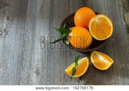 Whole and cut oranges with mint leaves close-up in a wicker basket on a wooden background. Top view
