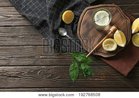 Composition with cold lemon water on wooden table