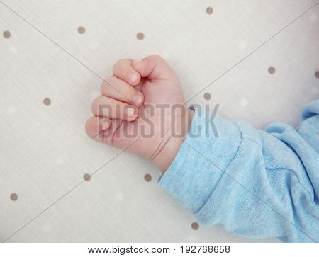 Hand of cute little baby sleeping on bed at home, closeup