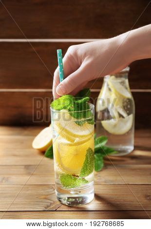 Female hand and glass of cold lemon water on wooden table