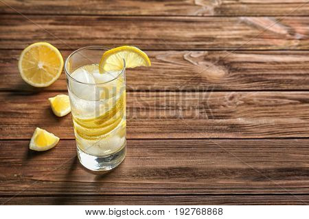 Glass of cold lemon water on wooden table