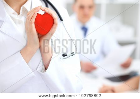 Female doctor with stethoscope holding heart.  Doctor and patient sitting in the background