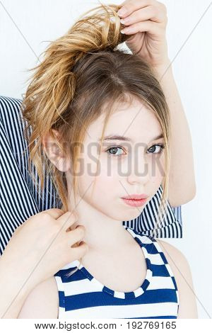 Cute girl playing with blond long hair standing near white wall hairstyle