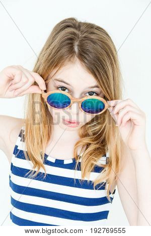 Cute blond girl eleven years old standing near white wall with green sunglass
