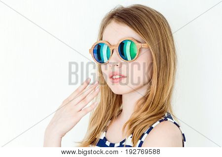 Portrait of blond girl in green sunglass on white