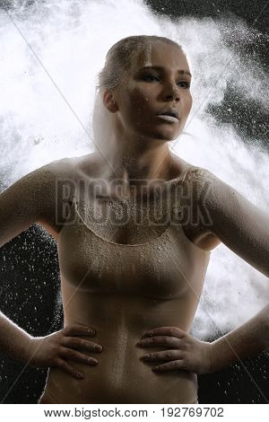 Young slim girl posing in white dust cloud artistic studio portrait