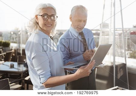Stay positive. Delighted female keeping smile on her face and wearing stylish glasses while using her computer for presentation