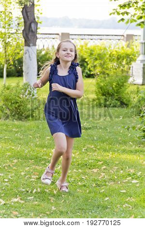 Cute running girl with disheveled hair in green park