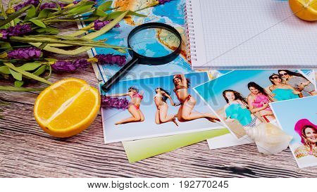 Beautiful color photographs of slender girls in bathing suits resting on the sea on a table with a map and magnifying glass.