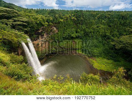 Sun illuminates the twin falls of Wailua waterfall on Hawaiian island of Kauai