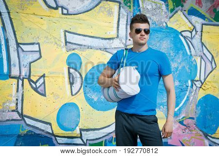 Young sportive man standing against a background of graffiti in a T-shirt shorts and sunglasses with a sports bag in his hand