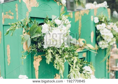 Beautifully decorated photo zona for a wedding. Green chest of drawers decorated with white flowers