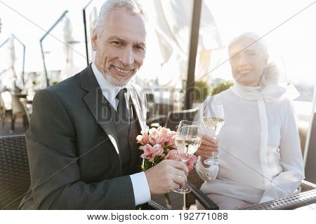 Lets touch our glasses. Self-confident male person holding glass with champagne in right hand and looking straight at camera while feeling happiness