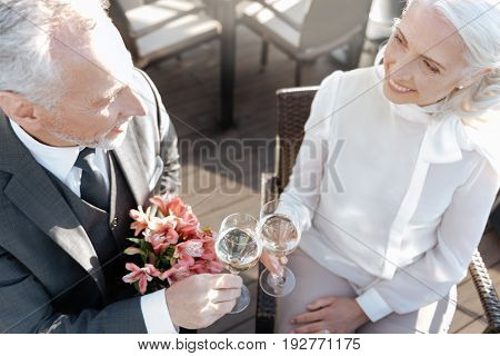 You look grate. Positive delighted couple touching glasses while sitting opposite each other and looking into eyes