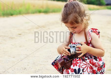 Happy little girl in retro outfit taking pictures with old film camera. Portrait of a cute preschool girl playing Outdoors
